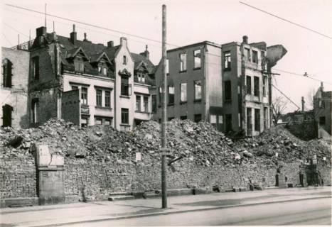 ARH Slg. Mütze 013, Trümmer hinter einer Trockenmauer und Holzmast für die Befestigung der Oberleitung der Straßenbahn in der Königstraße, Hannover, zwischen 1943/1949