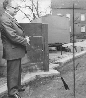 ARH Slg. Bartling 13, Ratsherr und Bürgermeister Herbert Gubba betrachtet eine Mauerecke, die in den Bürgersteig ragt (bei Firma Schlüter beim Umbau des Bahnhofs), 1974