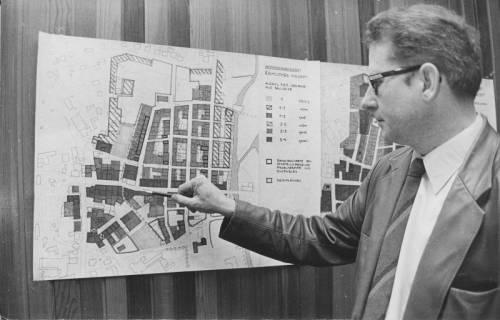 ARH Slg. Bartling 209, Stadtdirektor Felix Rohde zeigt auf eine an der Wandpaneele aufgehängte Karte mit dem räumlichen Konzept zum Stadtbild von Neustadt am Rübenberge, 1973