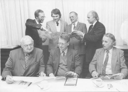 ARH Slg. Bartling 287, Gruppe von sieben Männern, davon drei Männer am Tisch sitzend, um 1980