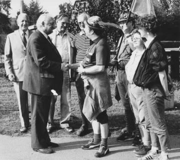 ARH Slg. Bartling 288, Henry Hahn, Bürgermeister, begrüßt eine Gruppe von Wanderern mit Fahne, darunter zwei Männer mit Trachtenhut, um 1980