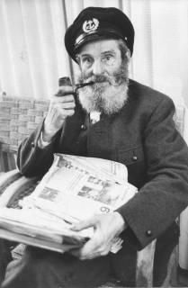 ARH Slg. Bartling 298, Clochard aus Paris mit Bart, Pfeife und Schiffermütze, auf einem Sessel sitzend mit Zeitungsstapel auf dem Schoß, 1973