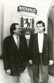 """ARH Slg. Bartling 317, Städtische Verwaltungsmitarbeiter Walter Berking (li.) und Michael Kugel vor dem """"Firmenschild"""" des Rathauses an der Theodor-Heuss-Straße 18, um 1990"""