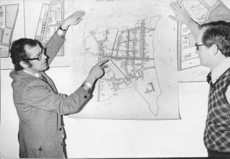 ARH Slg. Bartling 340, Städtischer Baudirektor Sigurd Trommer (li.) erläutert einen Stadtplan von Neustadt am Rübenberge., an der Wand gehalten von ihm und dem Angestellten Helmut Döring, 1974