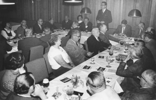 ARH Slg. Bartling 342, Stadtdirektor Felix Rohde, stehend, einen Vortrag haltend vor Männern und Frauen, die an Tischen im Hotel Scheve sitzen, 1971
