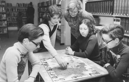 ARH Slg. Bartling 377, Vier Kinder in der Stadtbücherei am Tisch sitzend beim Würfelspiel unter den Augen von Gisela Kapp (1. hauptamtl. Leiterin der Bücherei), um 1970
