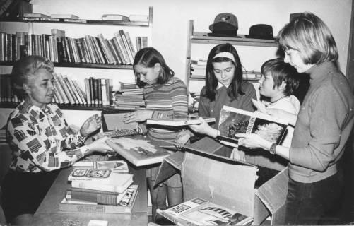 ARH Slg. Bartling 378, Vier Kinder helfen Frau Hoffmann (ehrenamtl. Mitarbeiterin) in der Stadtbücherei beim Auspacken von Büchern, 1971