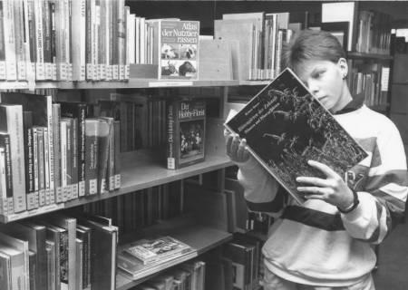 ARH Slg. Bartling 379, Jugendlicher beim Stöbern vor einem Bücherregal in der Stadtbücherei, um 1970