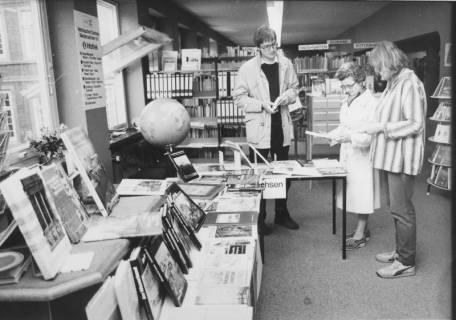 ARH Slg. Bartling 381, Kleine Buchausstellung mit auf Tischen ausgelegten Büchern über Niedersachsen mit drei interessierten Lesern, um 1970
