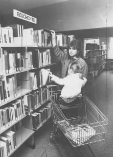 """ARH Slg. Bartling 382, Leserin mit Kind und Einkaufswagen vor dem Regal """"Geschichte"""" der Stadtbücherei, um 1970"""
