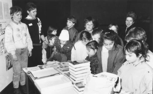 ARH Slg. Bartling 383, Gruppe von Kindern mit Lehrerin ? (rechts) vor einem Büchertisch in der Stadtbücherei, um 1970