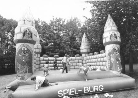 ARH Slg. Bartling 434, Spiel-Burg (Hüpfburg) mit spielenden Kindern im Park des Freibads, um 1980