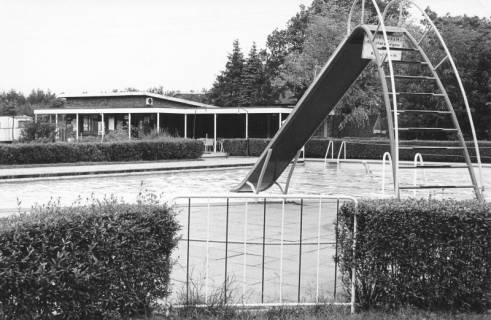 ARH Slg. Bartling 462, Blick über die Rutsche und das leere Schwimmerbecken auf das Servicegebäude des Freibads in Nöpke, um 1970