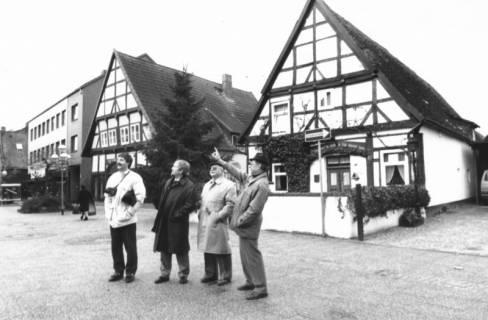 ARH Slg. Bartling 548, Giebel der beiden Fachwerkhäuser in der Windmühlenstraße 19 und 20, davor vier Männer, die das gegenüberliegende Haus am Hufeisenweg begutachten, um 1980
