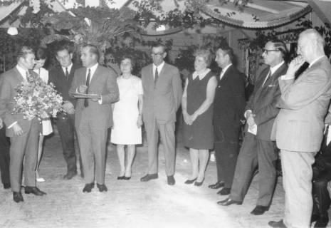 ARH Slg. Bartling 561, Kreis-Landvolkvorsitzender Friedrich Rohde (4. v. l.) überreicht Walter Seegers (l.) einen Blumenstrauß, daneben stehen sechs weitere Personen in einem festlich geschmückten Saal, 1970