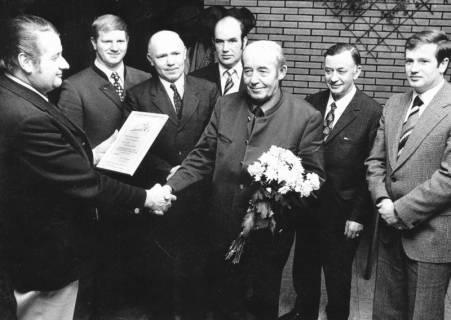 ARH Slg. Bartling 564, Inspektor Hoppenhöft überreicht einem älteren Landwirt eine Ehrenurkunde mit Blumenstrauß im Beisein von fünf weiteren Männern, 1974