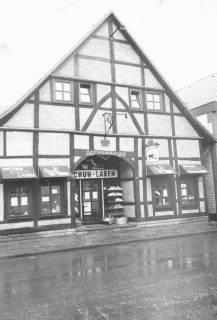 """ARH Slg. Bartling 578, Mittelstraße 17, Ackerbürgerhaus, renovierter Fachwerkbau von 1729 (lt. Balkeninschrift), """"Grüner Schuh-Laden"""", danach """"ABC-Schuhe"""", danach """"Rübenfaß"""" (Kneipe), um 1970"""