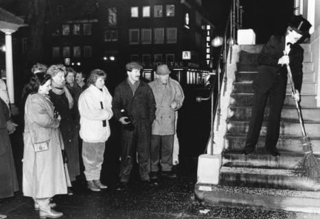 ARH Slg. Bartling 607, Junger Mann mit Zylinder beim Fegen der Rathaustreppe unter den Augen einer Gruppe von Zuschauern, um 1980