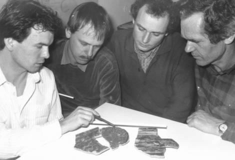 ARH Slg. Bartling 648, Vier Mitarbeiter des Bauamtes (?) am Tisch sitzend vor drei Scherben, um 1980