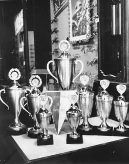 ARH Slg. Bartling 664, Marktstraße 15: Uhren, Schmuck, Augenoptik Butterbrodt (Inhaber: Klaus Meyer), Schaufenster mit Fußball-Pokalen unterschiedlicher Größe, darunter ein Wimpel des SV Scharrel, um 1975