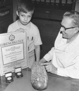 """ARH Slg. Bartling 665, Marktstraße 17: Bäckerei Robert Kemmerich; Großvater und Enkel (?) zeigen die DLG Ehrenurkunde samt silberner Preismünze für das """"Rübenberger"""" Brot, um 1975"""