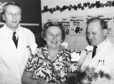 ARH Slg. Bartling 680, Marktstraße 1: Fritz Kollmeyer jun. (links) überreicht einer Frau einen Blumenstrauß im Verkaufsraum, 1968