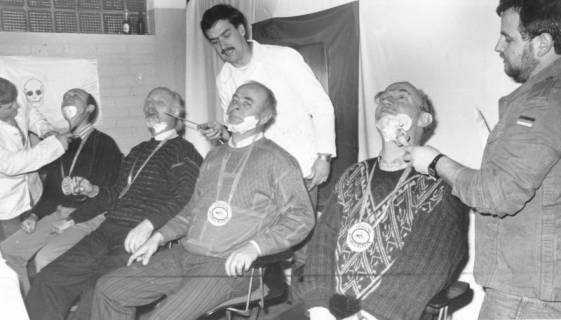 """ARH Slg. Bartling 681, Barbarafeier (?): vier Männer nebeneinandersitzend, mit einem """"Orden"""" von der """"Festung Wilhelmstein"""" auf der Brust, lassen sich den Bart für die Rasur einseifen (Mitte: Peter Weber?), 1968"""