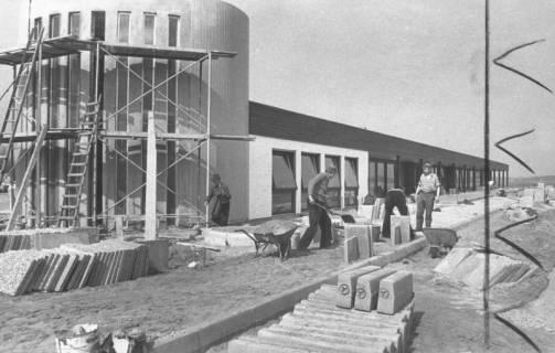 ARH Slg. Bartling 729, Großer Weg 45, Hibbe Wohnform GmbH & Co., Pflasterarbeiten vor dem im Rohbau fertiggestellten Möbelpavillon, Neustadt a. Rbge., um 1970