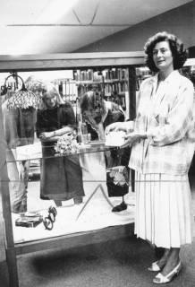 ARH Slg. Bartling 732, Frau N. N., einen Briefumschlag zeigend, vor einer Vitrine, dahinter drei junge Frauen, die Exponate in der Vitrine betrachtend, Neustadt a. Rbge., um 1970