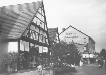 """ARH Slg. Bartling 768, Windmühlenstraße 17-20, Blick nach Norden Fahrrad Plinke (Giebelwand mit Werbung """"Komm ins Fahrradland""""), Geschäftsstelle der Leine-Zeitung (Schrägansicht des Giebels von Südosten), Neustadt a. Rbge., um 1980"""
