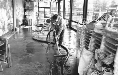 ARH Slg. Bartling 773, Marktstraße 26-27, Rückseite des Kaufhauses Hibbe, Reinigung des Steinfußbodens an der Fensterfront mit einem Staubsauger, Neustadt a. Rbge., um 1980