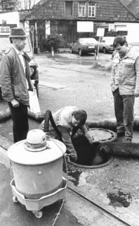 ARH Slg. Bartling 774, Marktstraße 26-27, hinter dem Kaufhaus Hibbe, Reinigung des Abwasserkanals an einem Revisionsschacht, Neustadt a. Rbge., um 1980