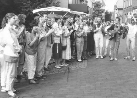 ARH Slg. Bartling 814, Musikalische Einlage eines singenden Gittaristen mitsamt applaudierenden Zuhörern auf der Marktstraße, Neustadt a. Rbge., um 1980
