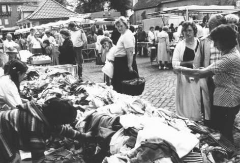 ARH Slg. Bartling 818, Verkauf von Textilien am Grabbeltisch, Blick über den Tisch auf das Wacht- und Spritzenhaus und die Kirche, Neustadt a. Rbge., um 1970