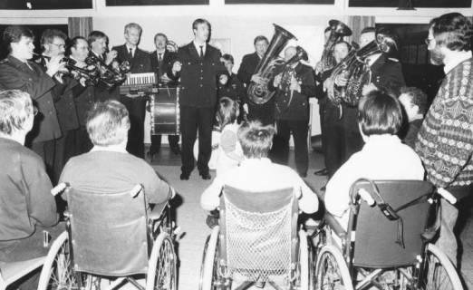ARH Slg. Bartling 1294, Feuerwehrkapelle spielt auf zur Weihnachtszeit, gesamtes Blasorchester, davor vier Zuhörer im Rollstuhl im Therapiezentrum des DRK, Mardorf, um 1970