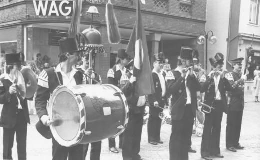 """ARH Slg. Bartling 1413, Die """"Bärenmusik"""" in Formation angetreten spielt auf der Marktstraße vor dem Textilkaufhaus Wage (Haus Nr. 18), Neustadt an Rübenberge, nach 1980"""