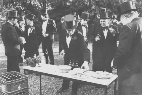 ARH Slg. Bartling 1418, Schützen in schwarzem Anzug und Zylinder beim Picknick im Freien mit Bier und Brötchen, Neustadt a. Rbge., um 1975