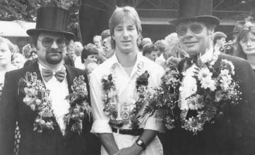 ARH Slg. Bartling 1426, Drei Schützenkönige mit umgehängten Blumenkränzen; in der Mitte der Jugend-Schützenkönig, Neustadt a. Rbge., um 1973