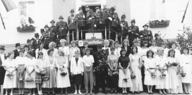 ARH Slg. Bartling 1431, Gruppenfoto der uniformierten Schützen mit Federhut auf der Treppe des alten Rathauses; vor der Treppe die Kranzdamen, in deren Mitte der Schützenkönig mit umgehängtem Eichenkranz, Neustadt a. Rbge, um 1973
