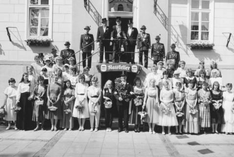ARH Slg. Bartling 1433, Gruppenfoto der uniformierten Schützen mit Federhut auf der Treppe des alten Rathauses; vor der Treppe die Kranzdamen, in deren Mitte der Schützenkönig mit umgehängtem Eichenkranz, Neustadt a. Rbge, um 1973