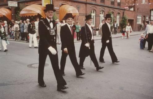 ARH Slg. Bartling 1435, Vier prominente Schützen mit Zylinder marschieren nebeneinander durch die Stadt über die Marktstraße (im Hintergrund die Fassade des Cafes Knoke), Neustadt a. Rbge, vor 1973
