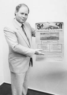 ARH Slg. Bartling 1437, Unbekannter Mann präsentiert das Plakat mit dem Programm des Schützenfestes vom 14.-16.06.1985, Neustadt a. Rbge, 1985
