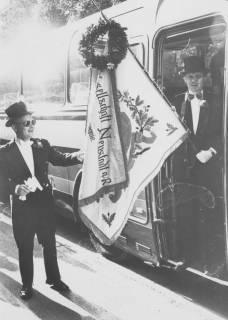 ARH Slg. Bartling 1442, Die Schützenfahne der ?? Compagnie (oben geschmückt mit einem Kranz) wird von zwei Schützen im Frack abgeholt, einer stehend in der Tür eines Busses, einer stehend vor der Tür eines Busses, Neustadt a. Rbge, um 1973