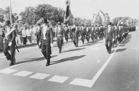 ARH Slg. Bartling 1445, Die Schützen in Festtagskleidung marschieren in Dreierreihe im Gleichschritt über die Leine-Brücke an der Herzog-Erich-Allee; im Hintergrund das Amtsgericht und das Gefängnis, Neustadt a. Rbge, um 1985