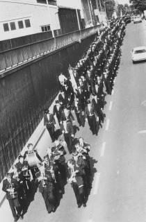 """ARH Slg. Bartling 1452, Die Schützen in Festtagskleidung marschieren in Dreierreihe durch die Straße """"Landwehr"""" von Westen in die Bahn-Unterführung, vorweg eine Blaskapelle, Blick von der Fußgängerbrücke auf die Stützmauer nach Südwesten, Neustadt a. Rbge, um 1985"""