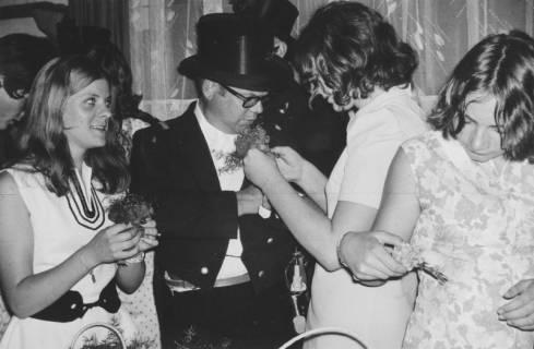 ARH Slg. Bartling 1461, Drei Kranzdamen schmücken den Ehrenhauptmann mit Ansteckblume am Revers des Fracks, Neustadt a. Rbge, 1970