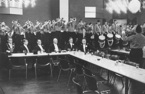 ARH Slg. Bartling 1462, Sechs Herren am Tisch sitzend beim Herrenessen im Festsaal des Freizeitzentrums (FZZ), dahinter auf der Bühne stehend ein Fanfarenkorps, Neustadt a. Rbge, 1972
