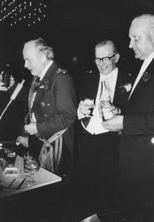 ARH Slg. Bartling 1468, Kommandeur Ulrich Schlüter im Offiziers-Frack mit Kommandeursschild und Schärpe bei einer Rede im Festsaal des FZZ, hinter ihm stehend im Frack zwei Männer (rechts: Hermann Sievers), Neustadt a. Rbge, um 1974