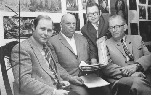 ARH Slg. Bartling 1470, Vier Mitglieder des Vorstandes sitzend vor Fotowand (von links: Herward Ladewig, Hermann Sievers, N. N., Robert Kemmerich), Neustadt a. Rbge, 1974