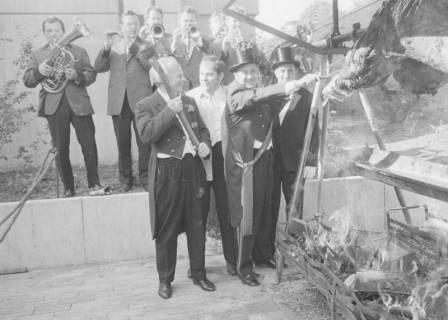 ARH Slg. Bartling 1473, Vier Vorstandsmitglieder an der Grillstation des Spanferkels (links: Ulrich Schlüter mit erhobener Axt), dahinter mehrere Blechbläser im Einsatz, Neustadt a. Rbge, um 1973